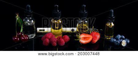 A long background of juicy berries of cherries strawberries blueberries and raspberries on black with a hatching. Next to an electronic cigarette and the fluidity for it