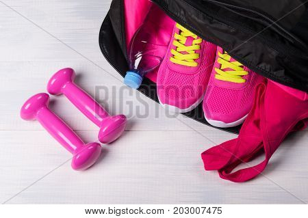 on the wooden floor sports bag with pink things in it uncovered and two dumbbells