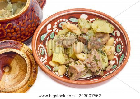 Ukrainian version of the dish Chanakhi - potatoes with meat mushrooms and haricot beans roasted in a clay pot in a clay bowl on a white background closeup