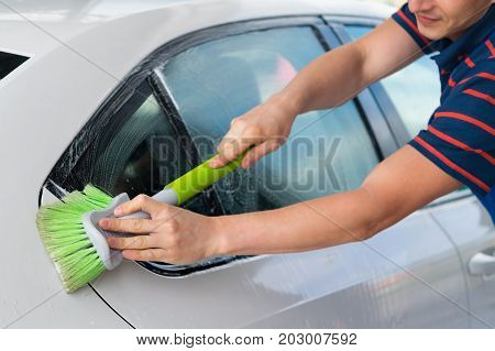White car wash with a green brush with foam
