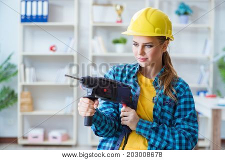 Woman in workshop with drilling drill
