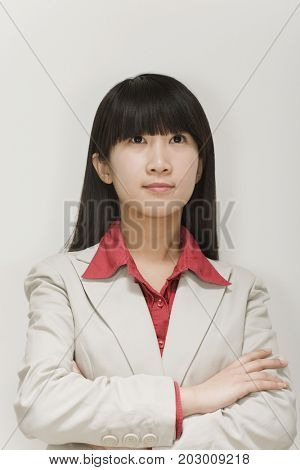 Chinese businesswoman looking up with arms crossed