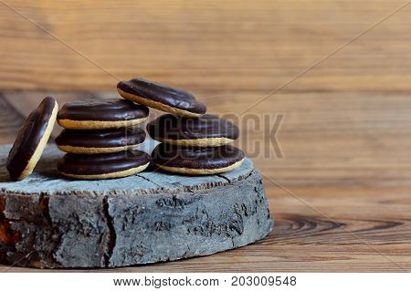 Chocolate glazed biscuits pile on a wooden background with copy space for text. Round biscuits in dark chocolate glaze icing