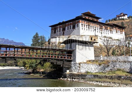 Paro Rinpung Dzong The traditional Bhutan palace with wooden bridge across the river Paro Chu near to the city Paro BHUTAN