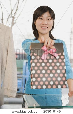 Chinese woman extending gift bag