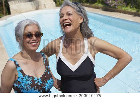 Friends at poolside in bathing suits and sunglasses