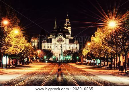 Main square with plague column national theatre and St. Elisabeth cathedral in Kosice Slovak republic. Night scene. Travel destination. Yellow photo filter.