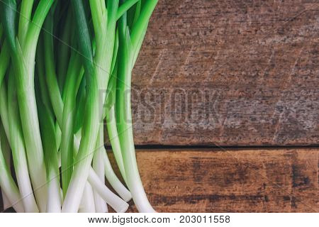 Fresh spring onion on wood table. Close up scallions or spring onion on wood plank in top view flat lay with copy space. Prepare spring onion for cooking. Food and vegetable concept for background. Scallions or spring onion on old plank.