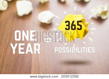 Inspiration quoteOne year equal 365 possibilities whit yellow paper ball floating at dark brown table topMotivational typographic.