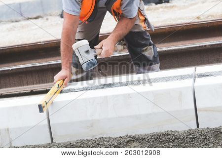 Construction worker leveling concrete pavement outdoors with hammer and bulb level.
