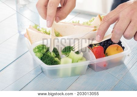 Young man eats a healthy meal from lunch box. Helpful Lunch concept