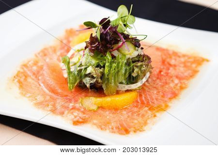 Trout carpaccio with citrus salad on a plate