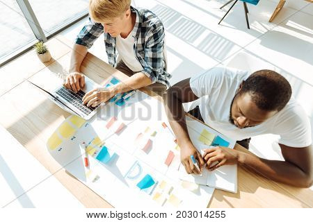 Involved in work. Top view of professional young colleagues sitting at the table and working while being involved in the project
