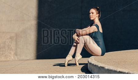 Ballet dancer sitting gracefully outdoors. Female ballet dancer sitting in pointe shoes resting her toes on the ground.