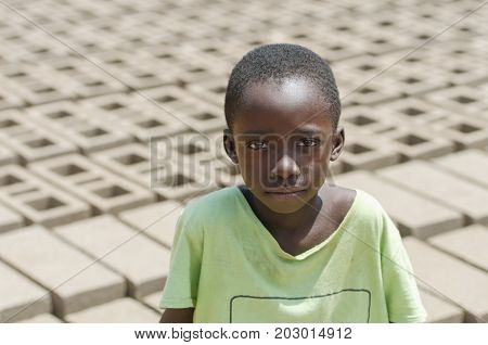 Black child sitting outdoors as a child labor concept - Isolated in front of a lot of bricks to build