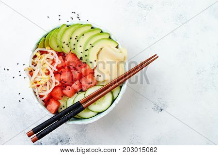 Hawaiian watermelon poke bowl with avocado cucumber mung bean sprouts and pickled ginger. Top view overhead flat lay copy space poster