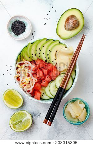Hawaiian watermelon poke bowl with avocado cucumber mung bean sprouts and pickled ginger. Top view overhead flat lay