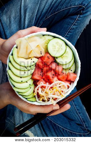 Girl in jeans holding hawaiian watermelon poke bowl with avocado cucumber mung bean sprouts and pickled ginger. Top view overhead