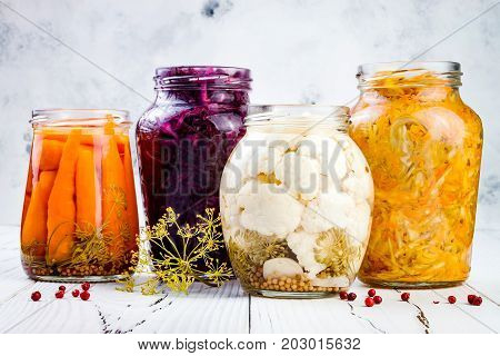 Sauerkraut variety preserving jars. Homemade red cabbage beetroot kraut turmeric yellow kraut marinated cauliflower and carrots pickles. Fermented food.