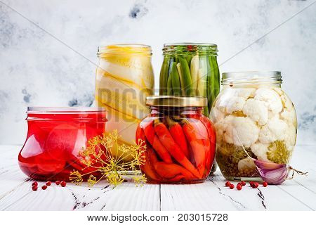 Marinated pickles variety preserving jars. Homemade green beans squash radish red chili peppers cauliflower pickles. Fermented food.