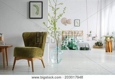 Green vintage chair next to wooden table with handmade lamp in simple bedroom with tree branch in decorative vase