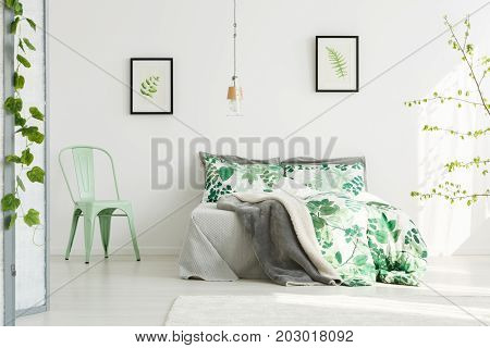 Mint chair next to king-size bed with floral bedsheets in inspiring bedroom with leaves paintings