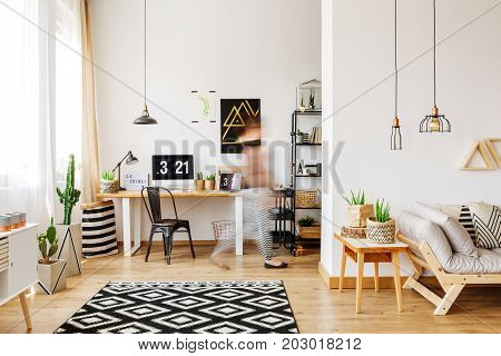Home furniture of a freelancer with natural eco accessories wooden desk potted plants patterned rug computer and triangle shelves in spacious living room