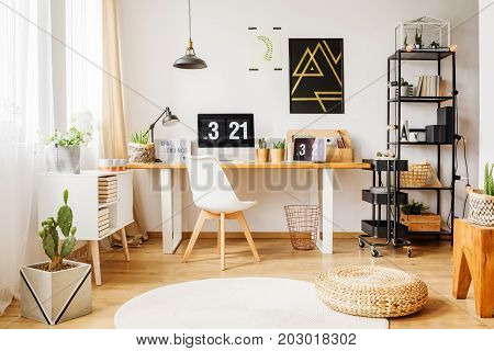 Scandinavian room in contemporary loft with minimalist poster on white wall window wooden furniture and black simple accessories