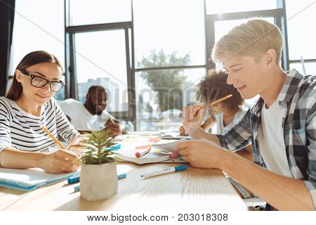 Campus life. Cheerful young students sitting in the cafeteria and doing their home assignment while enjoying students life