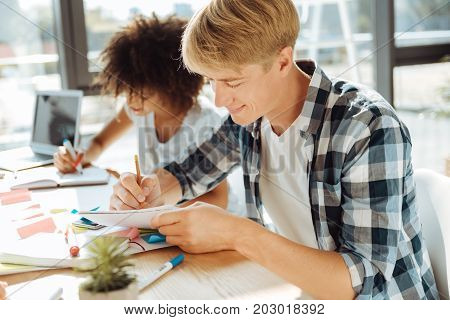 Broaden your mind. Positive male student making notes and sitting at the table while studying with his groupmate