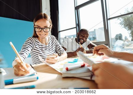 Smart and intelligent. Cheerful beautiful female student sitting at the table in the cafeteria and studying while with her groupmates