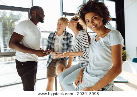 Full of positivity. Cheerful smiling afro american woman leaning on the table while resting with her university friends