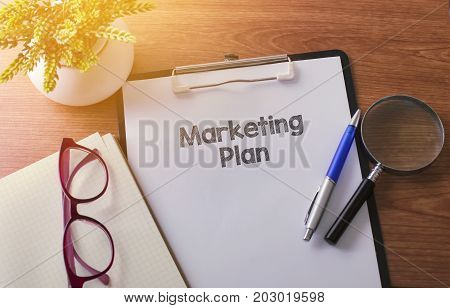 Marketing Plan Word On Paper With Glass Ballpen And Green Plant.