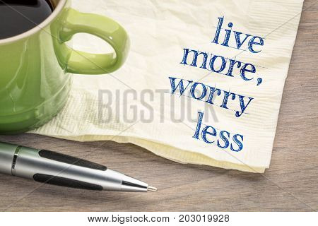 live more, worry less text - inspirational handwriting on a napkin with a cup of coffee