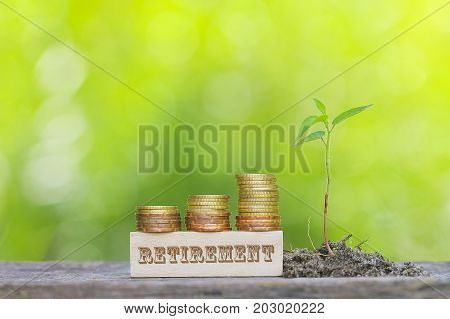 RETIREMENT Golden coin stacked with wooden bar on shallow DOF green background