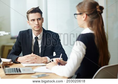Young applicant listening to employer question during interview
