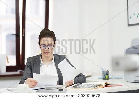 Young accountant with papers analyzing data by workplace