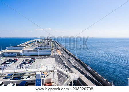 panoramic bird eye top aerial view with beautiful sea level with highway road under dramatic clear glow and fantasy blue sky in Umi Hotaru parking area island Tokyo bay aqua line Japan