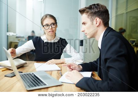 Confident manager explaining her colleague online data on laptop display