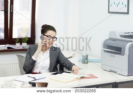 Young female economist speaking by smartphone and making notes in copybook by workplace