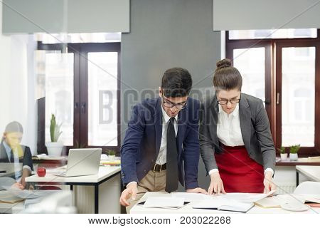 Two economists brainstorming while looking through data and preparing financial report