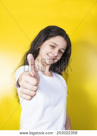 Beautiful Young Girl Smiling Extends A Hand Forward And Shows Gesture Class.yellow Background