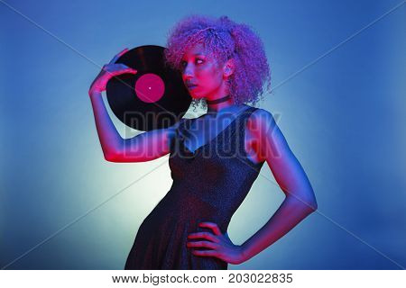 black woman with groovy hair holding an old eighties vinyl with retro disco lights