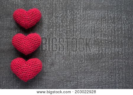 Three crocheted red hearts on a black grunge board.