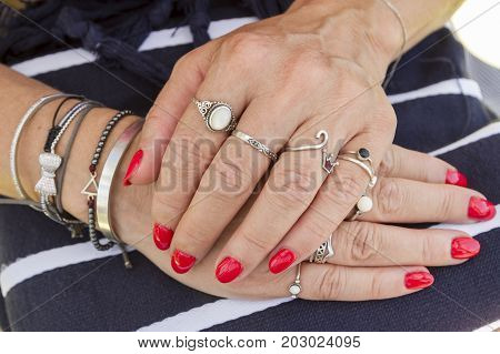 Various Silver Rings With Red Manicured Fingernails. Soft Focus