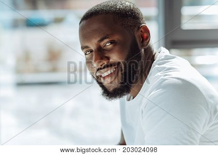 Confident glance. Joyful handsome young afro american man smiling and posing in front of the camera while feelign glad