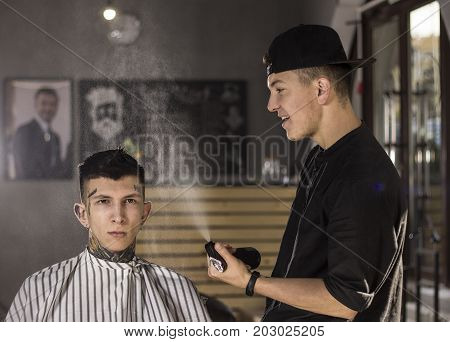 Making haircut look perfect. Young man  is prepared to get haircut by happy barber while sitting in chair at barbershop
