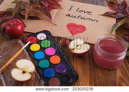 Autumn composition with leaves, apples, water-colours and a sketch book with a sign I love autumn and heart in it.