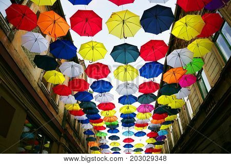 Colorful umbrellas background. Colourful umbrellas urban street decoration. Hanging Multicoloured umbrellas over blue sky. Bright Colors backdrop.
