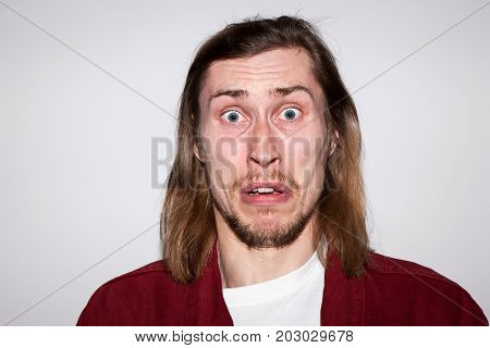Scared male. Surprising news for young man. Terrified guy portrait, fear emotion concept